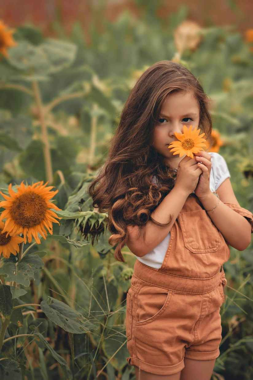 photo of girl in orange dungaree holding sunflower